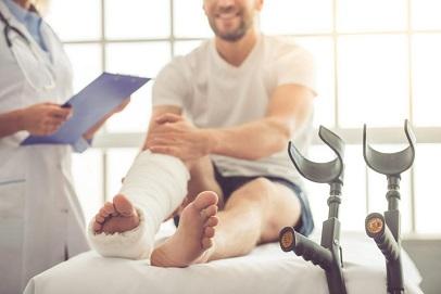мъж с гипс и патерици върху легло
